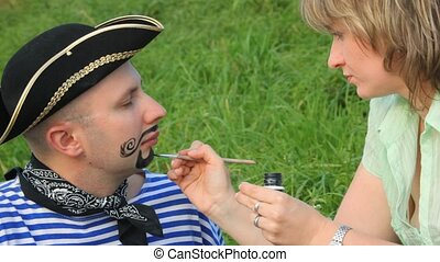 woman drawing beard and moustaches on face of man in pirate...
