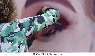 Woman drawing graffiti portrait