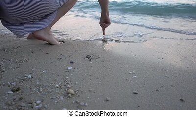Woman drawing heart in the beach sand