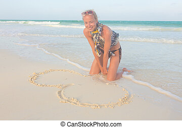 Woman drawing heart on the sand.