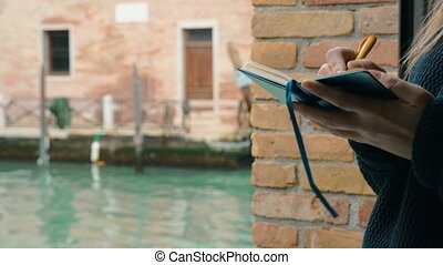 Woman drawing in sketch-book by the water