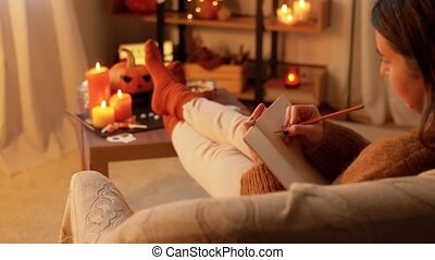 halloween, holidays and leisure concept - young woman with pencil drawing in sketchbook or diary and resting her feet on table at cozy home