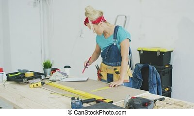 Woman drawing line on plywood in workshop - Beautiful blond...