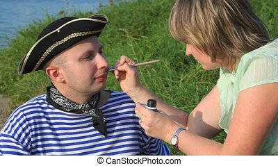 woman drawing moustaches on face of man in pirate costume