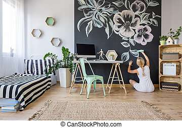 Woman drawing on chalkboard wall