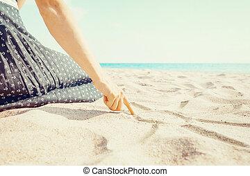 Woman drawing on sand beach.