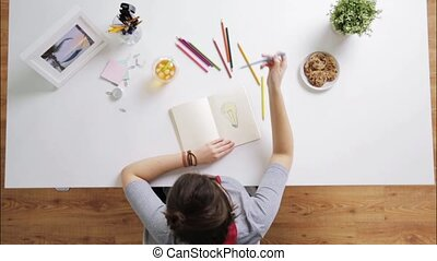 woman drawing picture in notebook at home desk - people,...