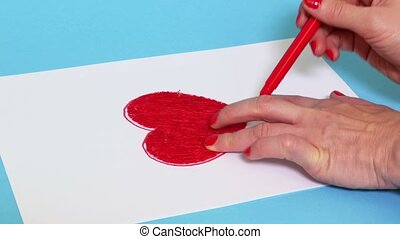 Woman drawing red heart shape