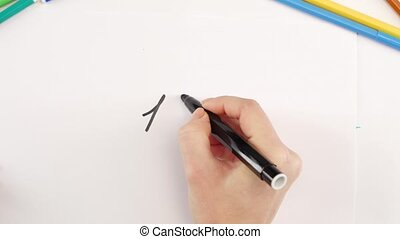 Womans hand drawing the 100 percent using black felt-tip pen on white paper among other colored felt-tips