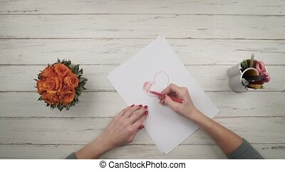 Woman draws a heart on a white sheet of paper. Top view. Hands close up view