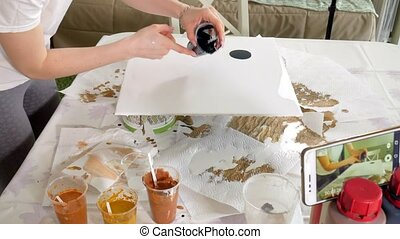 woman draws a picture of a fluid art on canvas