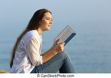 Woman dreaming reading a book on the beach