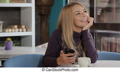 Woman dreaming with smartphone in her hand at the cafe