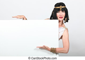 Woman dressed as Egyptian holding message board
