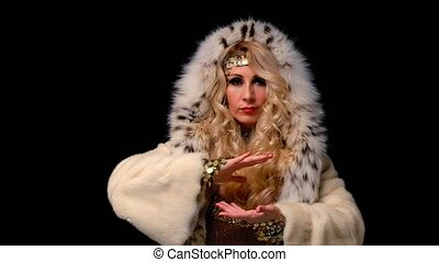 Woman dressed in a fur coat moves hands in Qigong style