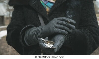 Woman dressed in black gloves smokes a cigarette
