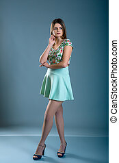woman dressed in green dress over blue grey background
