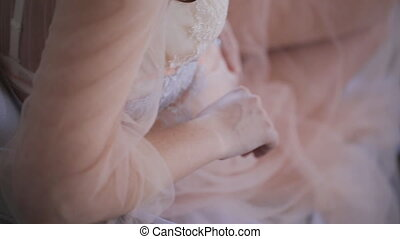 Woman dressed in light pink guipure clothes sits on floor
