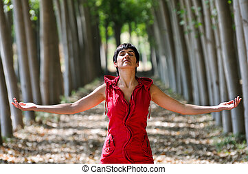 Woman dressed in red, meditating in the forest