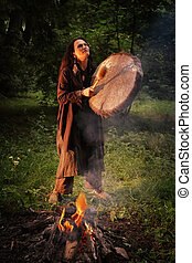 Woman dressed in shaman costume playing on shaman drum near large fire