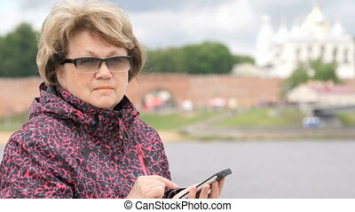 Woman dressed in sport jacket holding mobile phone