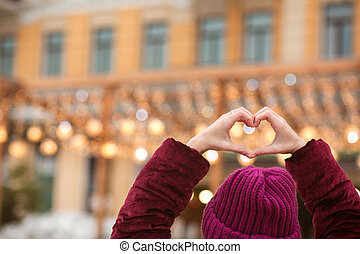 Woman dressed in warm clothes making heart shape from her hands on a background of city lights. Empty space