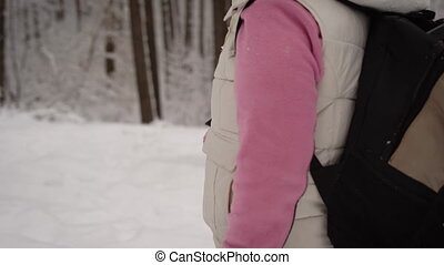 Woman dressed in warm sports clothes with a backpack actively walking on  footpath in the forest holding in her hands  special sticks for fitness.