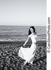 Woman dressed in white barefoot on the beach sand