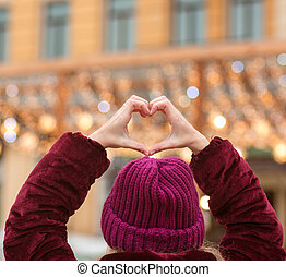Woman dressed in winter clothes making heart shape from her hands on a background of city lights