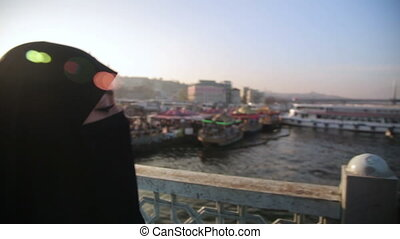 Woman dressed with black headscarf, chador on istanbul...