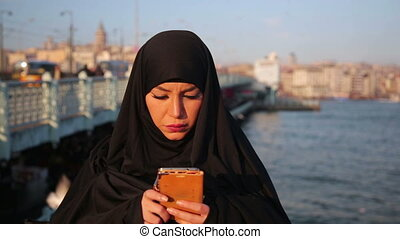 Woman dressed with black headscarf, chador using mobile phone