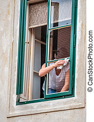 woman dressing a window