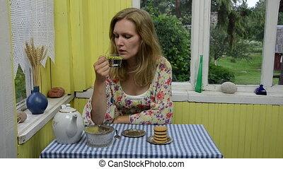 woman drink camomile tea - Woman drink herbal camomile tea...