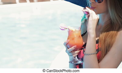 Woman drink cocktail near the swimming pool