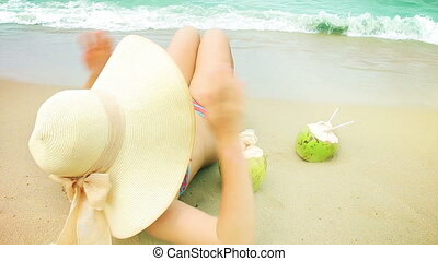 Woman drink coconut on a beach.