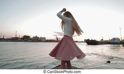 woman drink cofee watching at sunset jumping and dancing river port