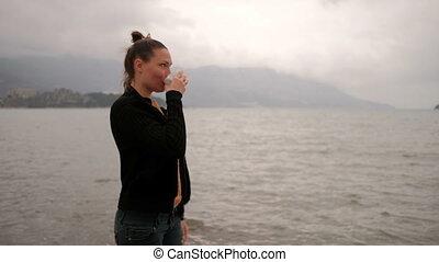 Woman drink coffee standing on lake coast, camera go counterclockwise.