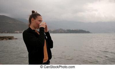 Woman drink coffee standing on lake coast, camera go clockwise.