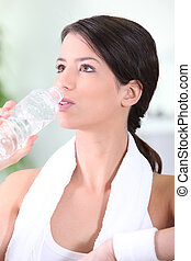 Woman drinking a bottle of water after a workout