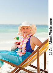 Woman drinking a cocktail in her deck chair