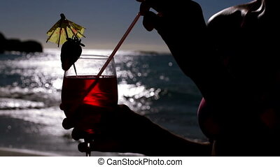 Woman drinking a cocktail on the beach