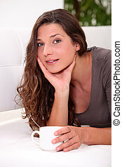Woman drinking a cup of coffee in her living room