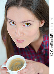 Woman drinking a cup of coffee on the sofa