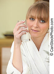 Woman drinking a glass of milk in her bathrobe