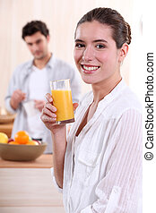 Woman drinking a glass of orange juice for breakfast