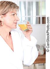 Woman drinking a glass of orange juice
