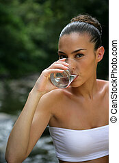 Woman drinking a glass of water by a river