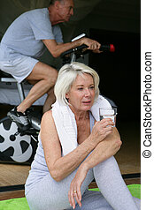Woman drinking a glass of water during a workout