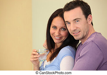 Woman drinking a glass of water in the arms of her husband