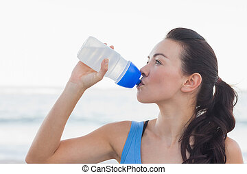 Woman drinking after exercising